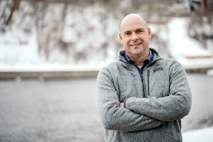 Matt Simcik smiling along a riverbank in winter.
