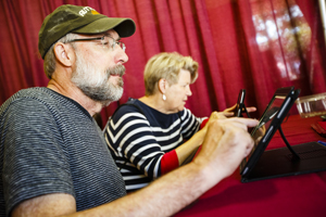 A man and a woman using iPad tablets.