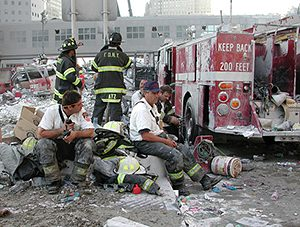 A group of firefighters sitting on piles of rubble in the street.