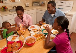 A family of four sits at a kitchen table to eat dinner.