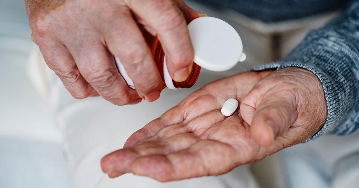 The hands of an elderly man holding a pill.