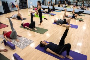 Students practice yoga during a class