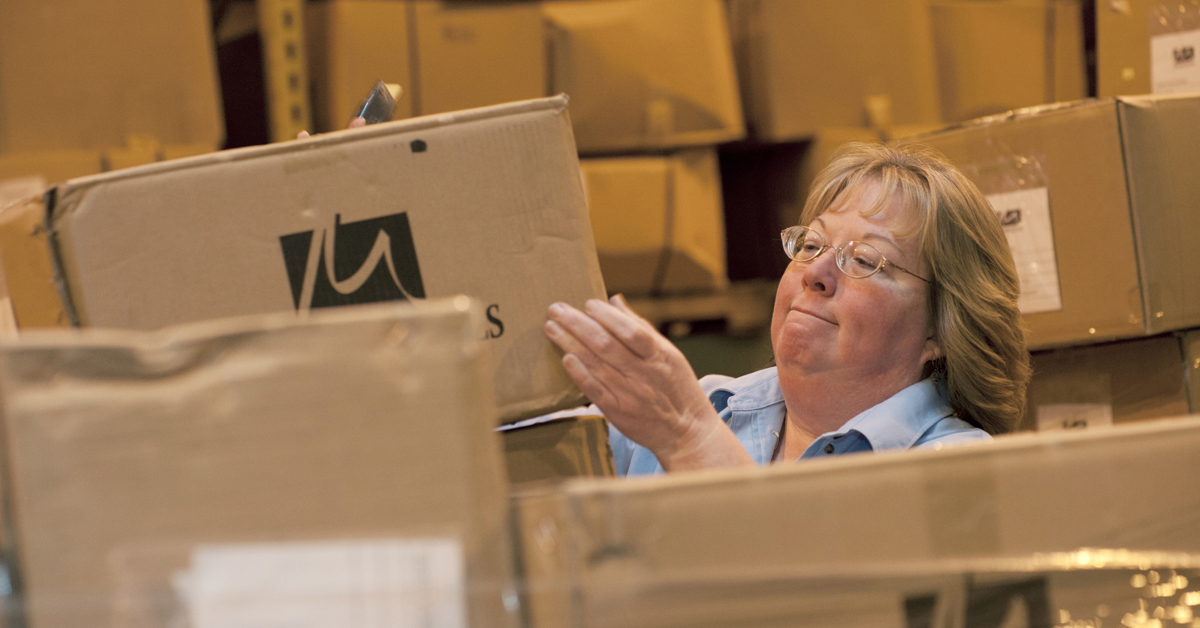 A worker inspects boxes of linens.