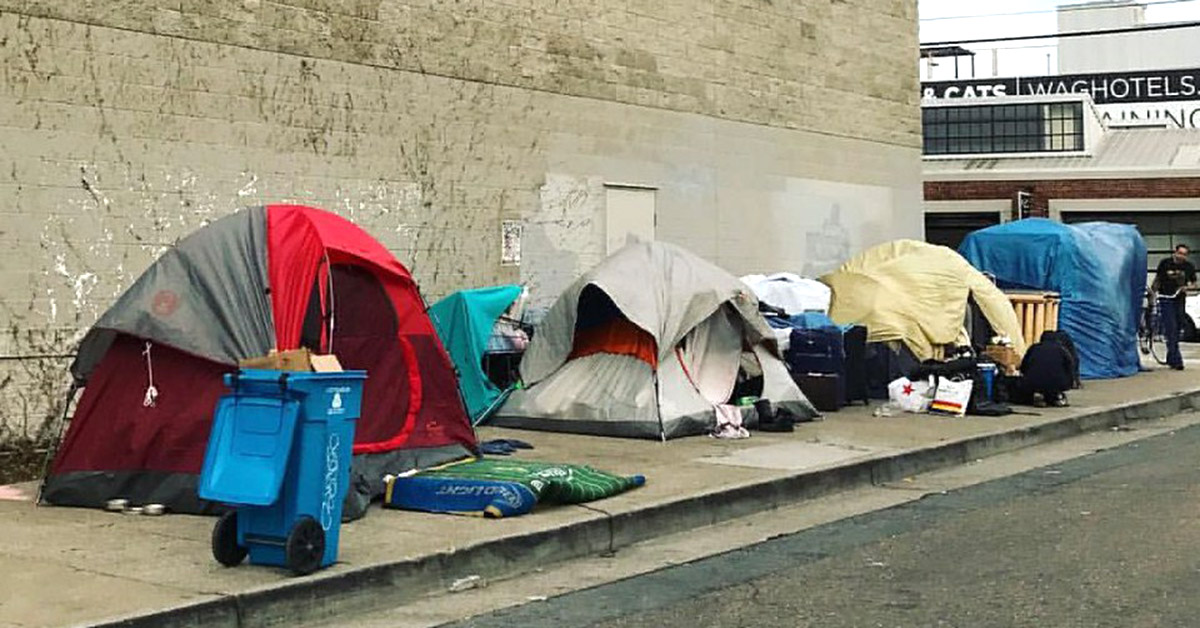 A row of tents standing alongside a building.