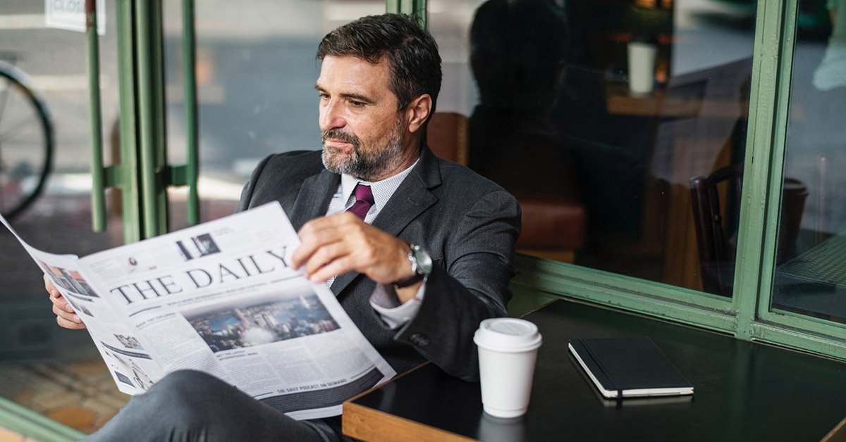 A man in a business suit reading a newspaper