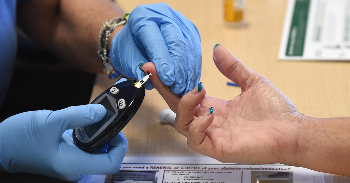 A woman getting her finger pricked for a blood glucose check.