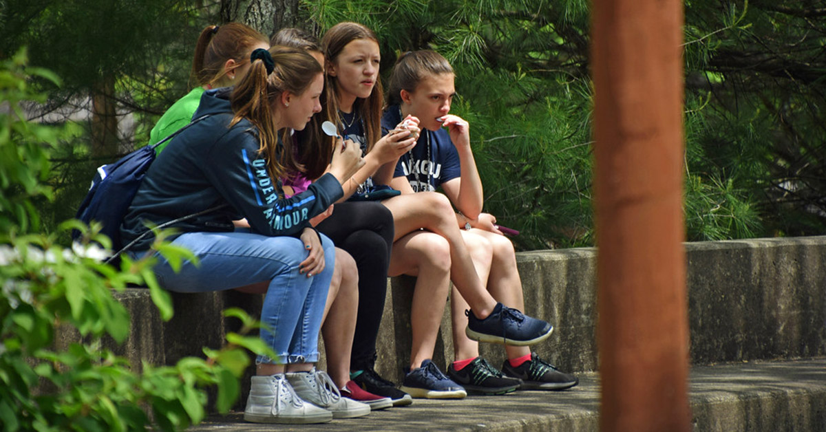Teenagers sit on a wall eating snacks.