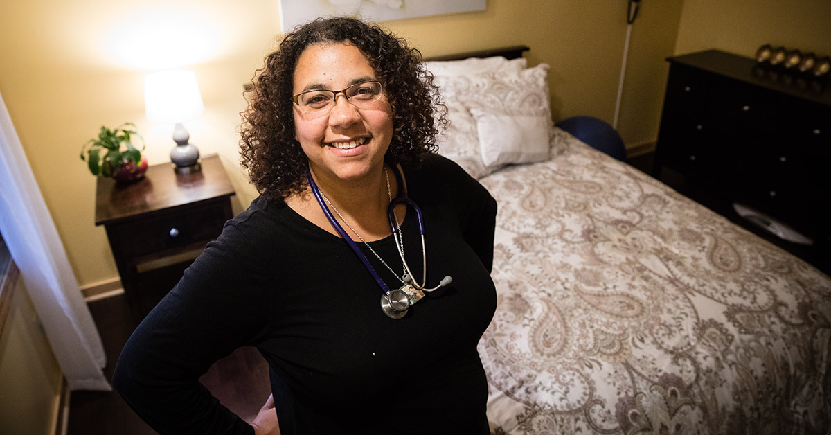 A midwife smiling inside a bedroom of a birthing center.