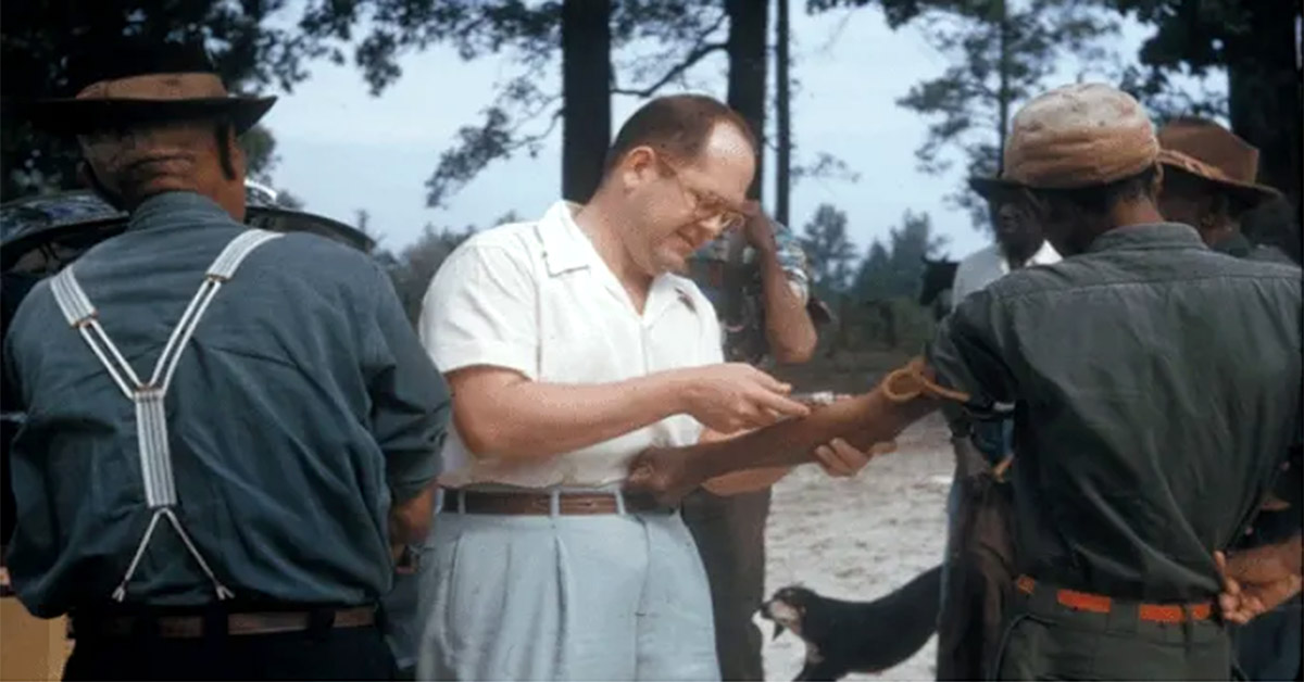 A man takes a blood sample from the arm of a Tuskegee resident.