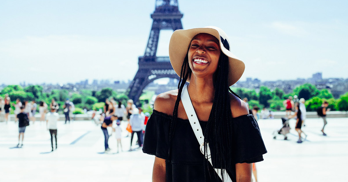 A young woman posing in front of the Eiffel Tower in Paris.