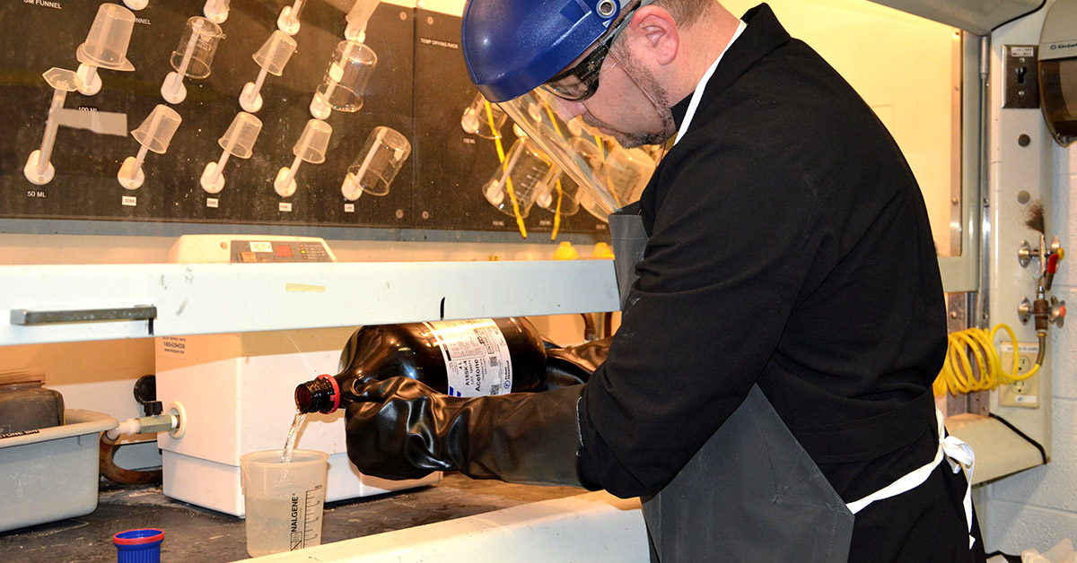 A lab technician pours a chemical into a container.