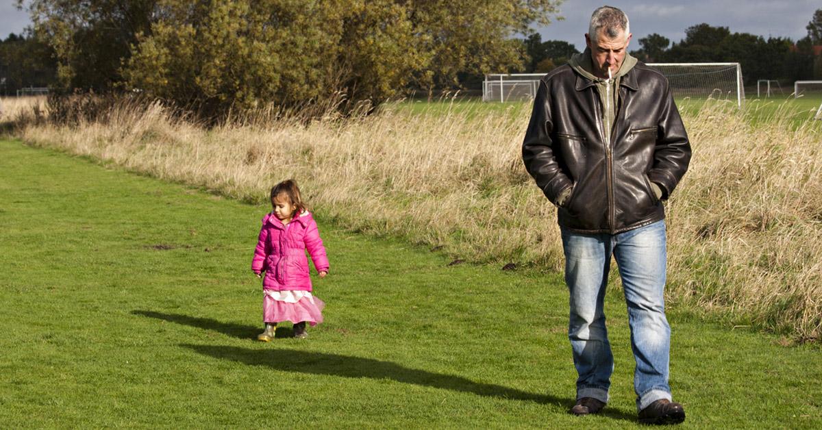 A little girl walking with an older man smoking a cigarette