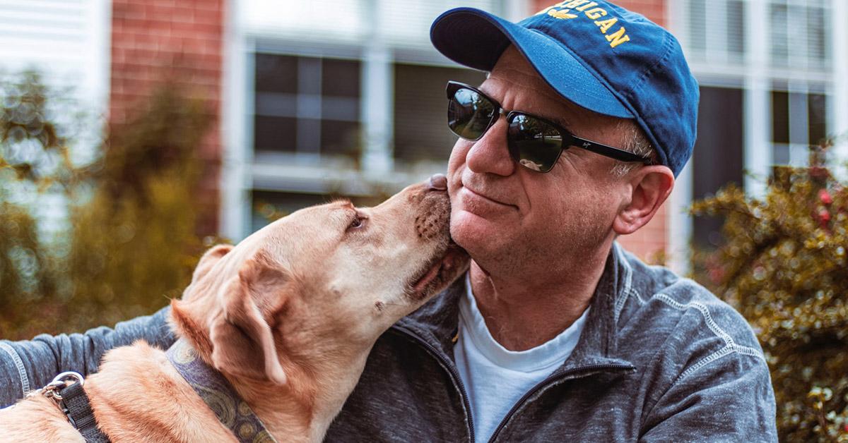 A dog licking a man's face.