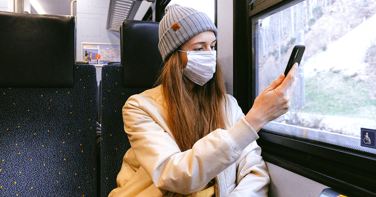 Woman wearing a surgical mask using her phone.