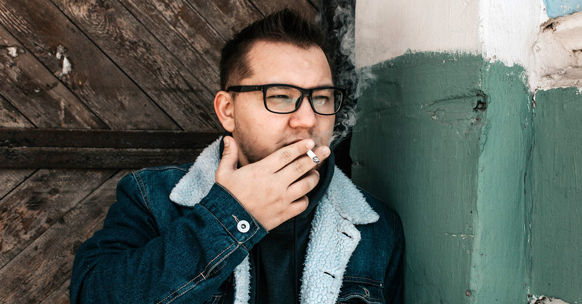 A man smoking a cigarette outside of a building.
