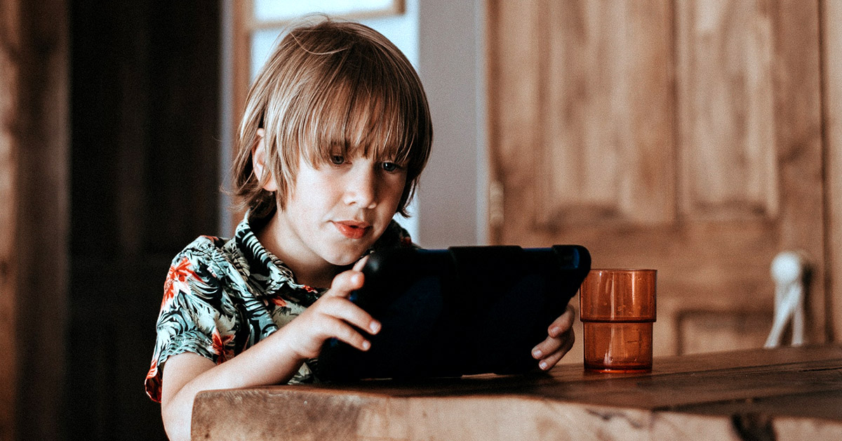 A young boy seated at a table using a tablet computer.
