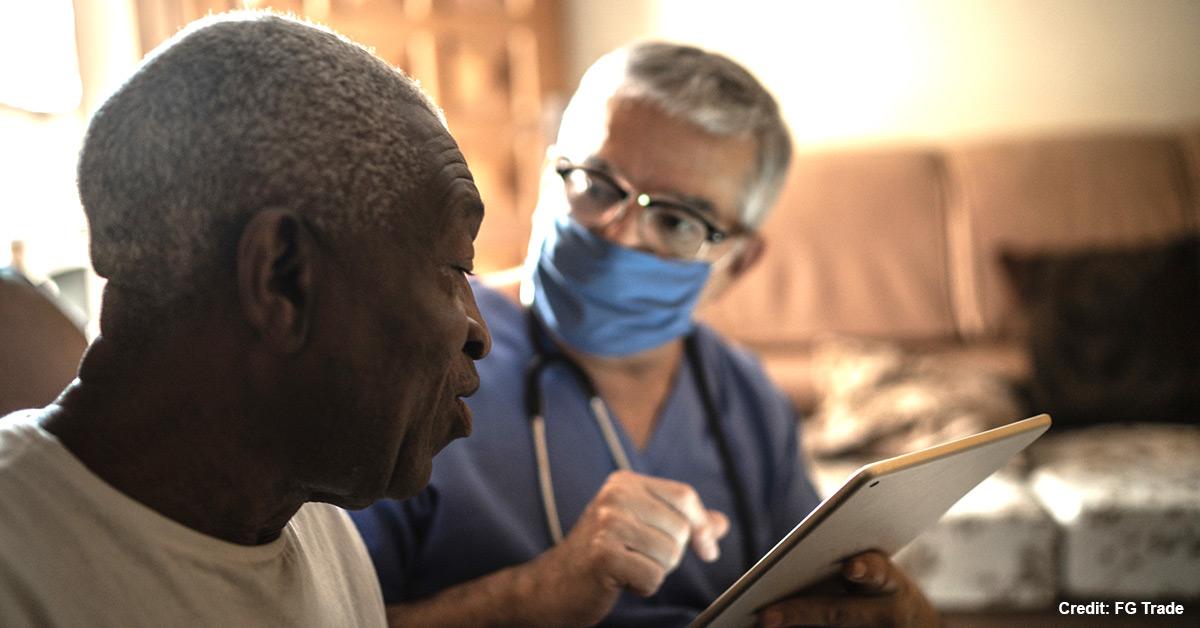 A nurse talks to a Black resident.