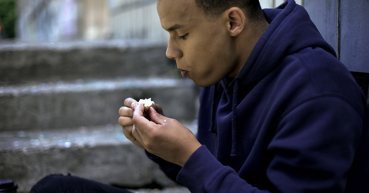 A teenage eating the last bite of a sandwich.