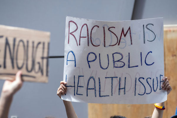 protester holding up sign that says racism is a public health issue