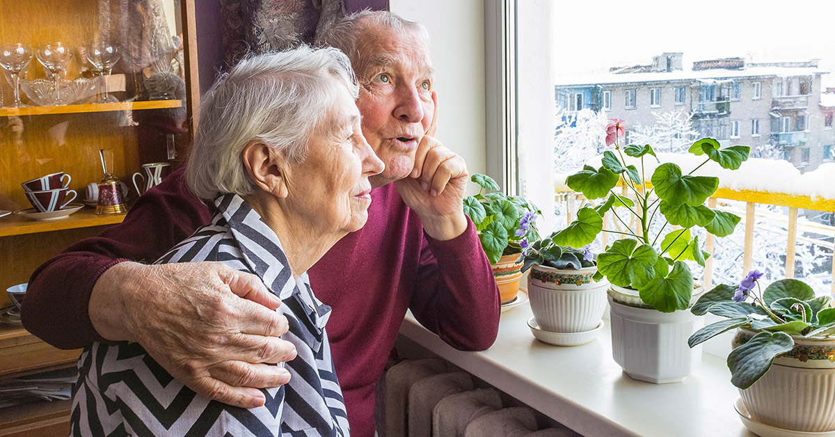 An elderly man and woman cuddle while looking out a window.