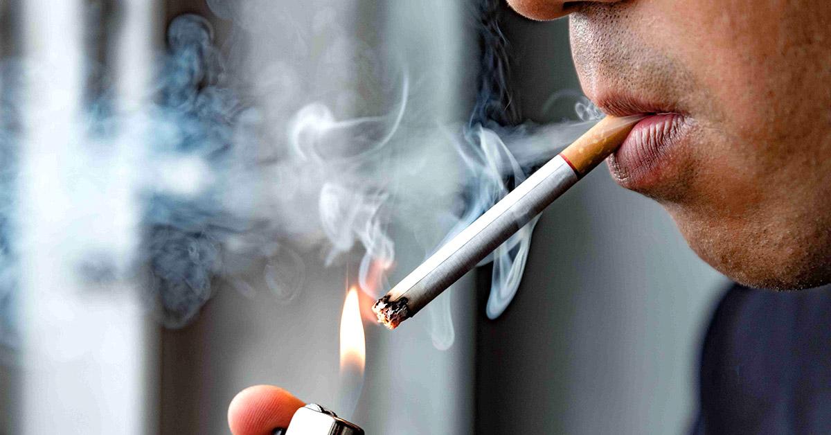 A man lights a cigarette.