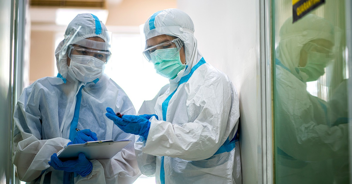 Two providers in PPE stand in a doorway.