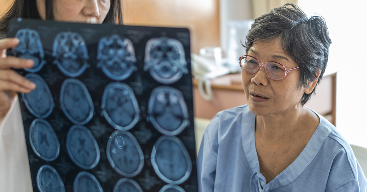An Asian female patient looks at brain scan images with a doctor.