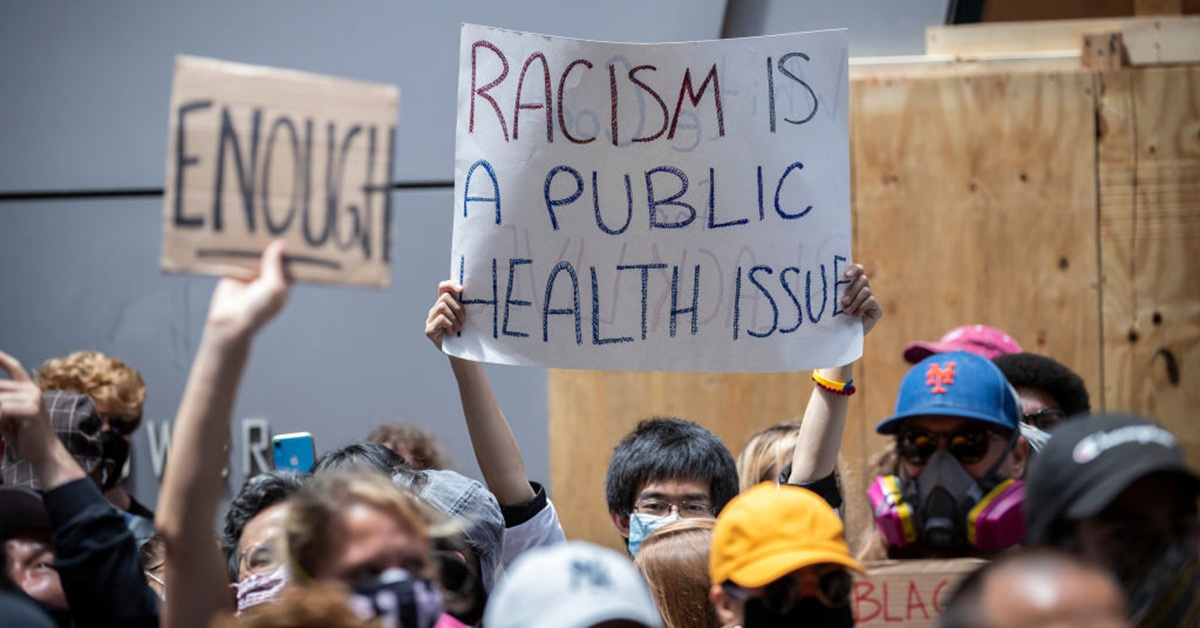 In a crowd of protestors, a man holds a sign reading racism is a public health issue.