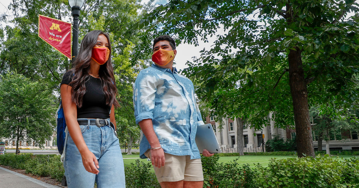 Two students walking on campus with masks