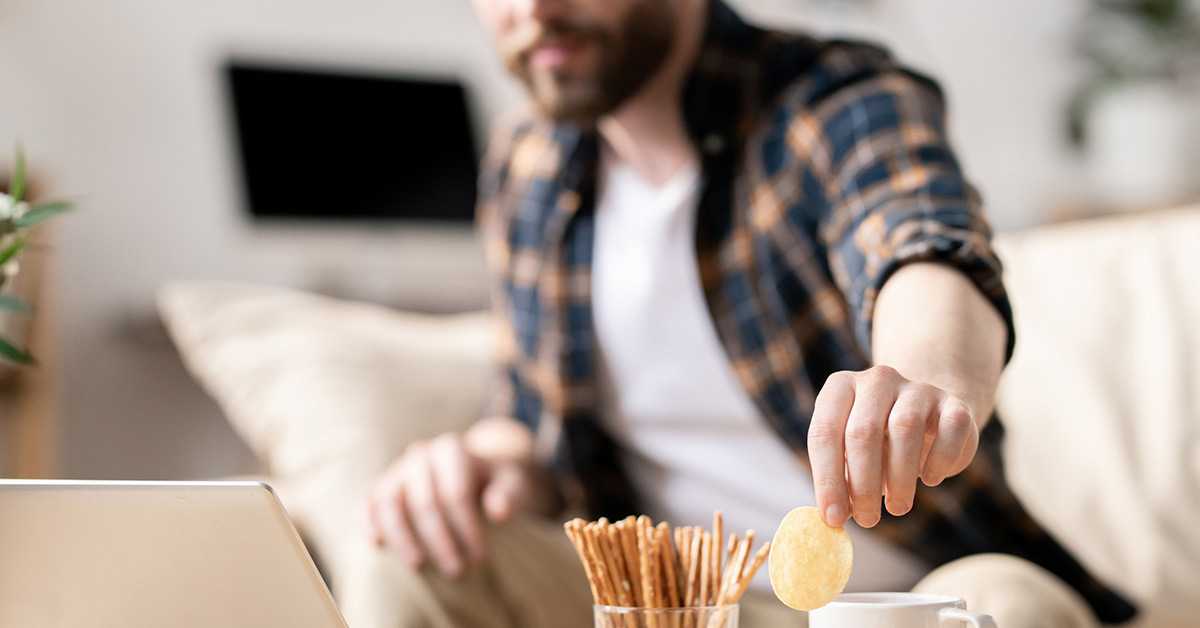 A man grabs a potato chip while working on his laptop from a living room.