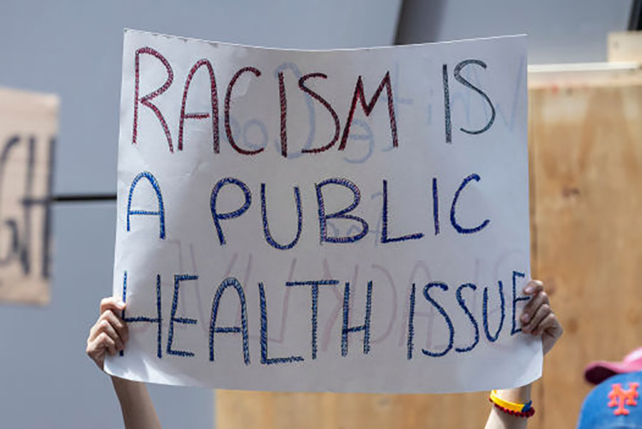 protest sign that reads: racism is a public health issue