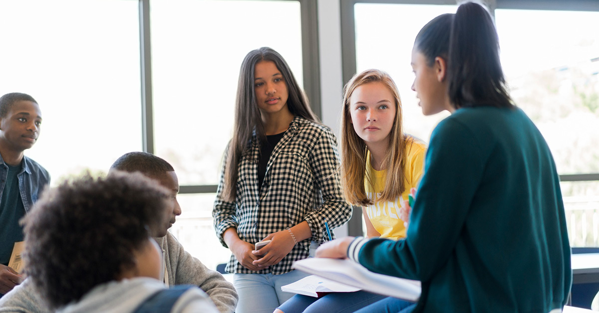 A group of teens talking in a classroom.