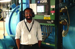 University of Washington student and MnTAP intern Daniel Sales with one of IBM's HVAC systems. Photo by Brian Morgan